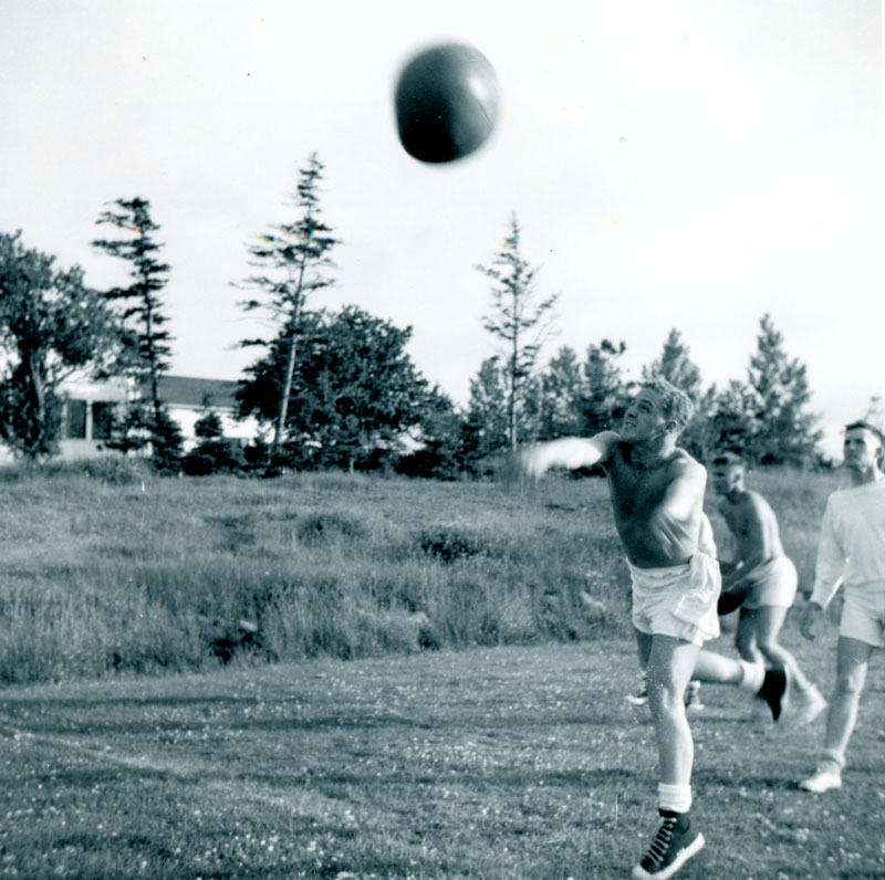 UNTD Sports Tabloid, HMCS Cornwallis, July 1964, Ray Mofford throwing medicine ball; David Cooper behind in white, Peter Kincaid no top, all Haida Division.